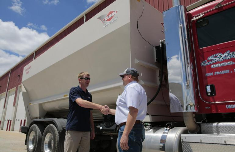 A KUHN Dealer shaking hands with a customer while standing in front of a KUHN Knight ProFeed delivery box.