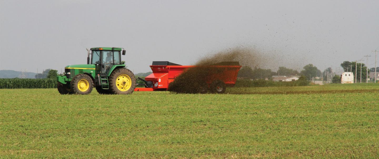 Side view of a SL 124 spreading liquid slurry in a field.