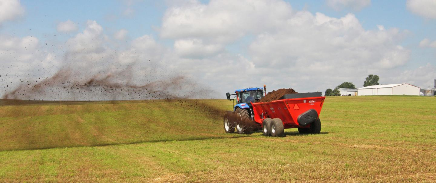 A rear shot of a SL 124 spreading manure in a hay field.