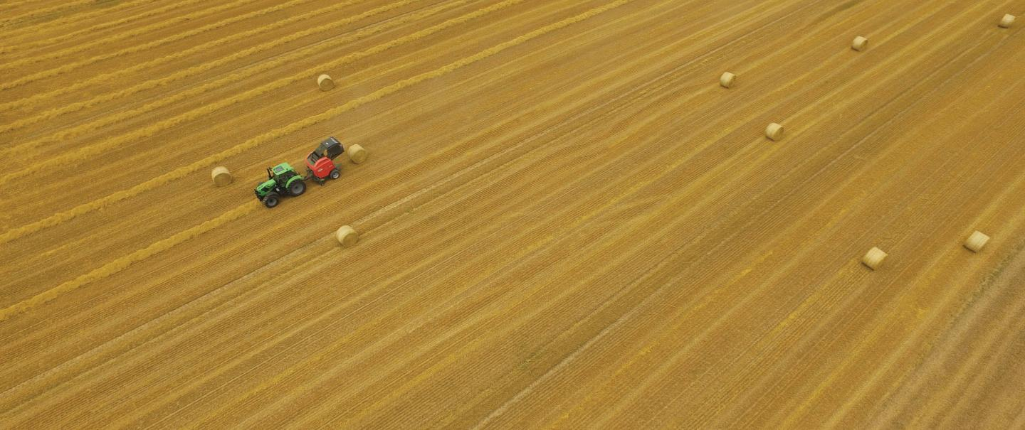 An overhead shot looking down on a VB 3195 baling straw, surrounded by many bales