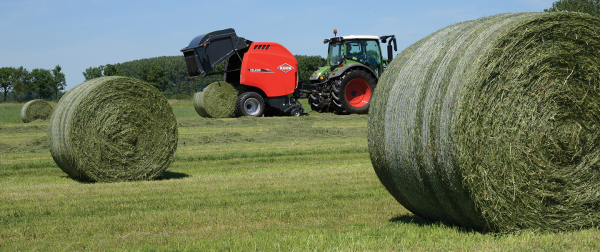 KUHN VB 3100 Series round baler baling hay with round hay bales in the foreground.